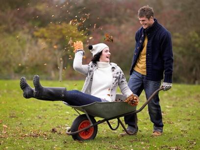 Casal brincando no jardim com carrinho de mão