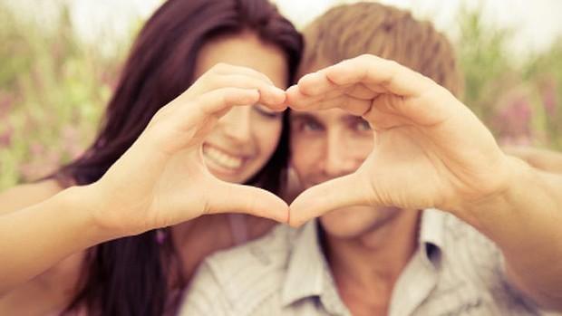 Casal fazendo coração com as mãos