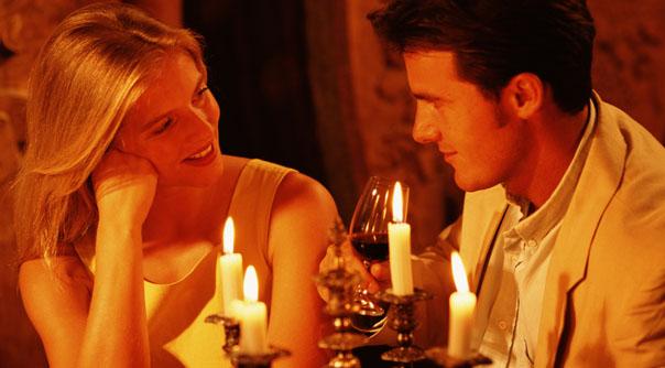 Casal jantando à luz de velas