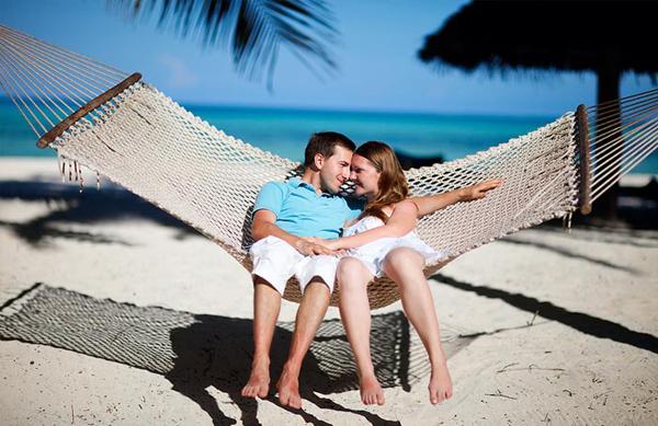 Casal na praia balançando na rede