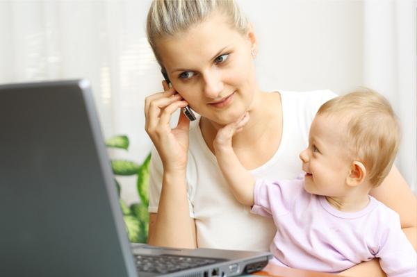 Mãe trabalhando com filho no colo e atendendo o celular