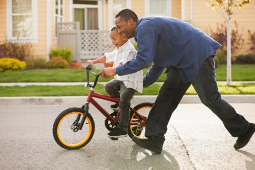 Pai ensinando filho a andar bicicleta