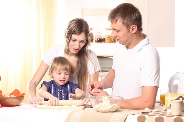 Pais ensinando filha a fazer massa