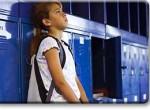 Foto de criança chateada encostada no armário da escola